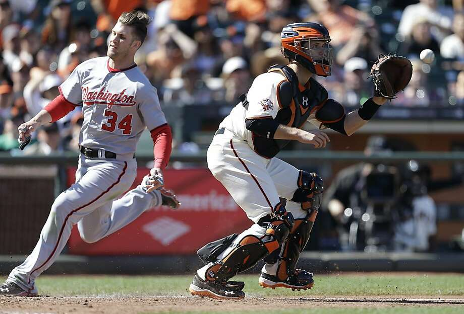 Washington Nationals' Bryce Harper, left, scores behind San Francisco Giants catcher Buster Posey in the 10th inning of a baseball game Wednesday, May 22, 2013, in San Francisco. Harper scored on a hit by Nationals' Ian Desmond. (AP Photo/Ben Margot) Photo: Ben Margot, Associated Press