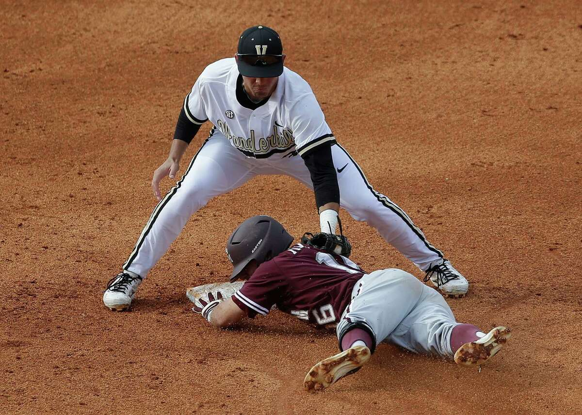 Texas A&M's Mikey Reynolds (16) slides safely into second on an rbi double in the fifth inning of their Southeastern Conference Tournament baseball game at the Hoover Met in Hoover, Ala., Wednesday, May 22, 2013. Defending is Vanderbilt's Vince Conde. (AP Photo/Dave Martin)