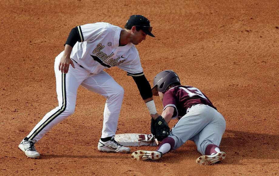 Texas A&M's Krey Bratsen (13) slides safely under the tag of Vanderbilt' shortstop Vince Conde on a steal in the fifth inning of their Southeastern Conference Tournament college baseball game at the Hoover Met in Hoover, Ala., Wednesday, May 22, 2013. (AP Photo/Dave Martin) Photo: Dave Martin, Associated Press / AP