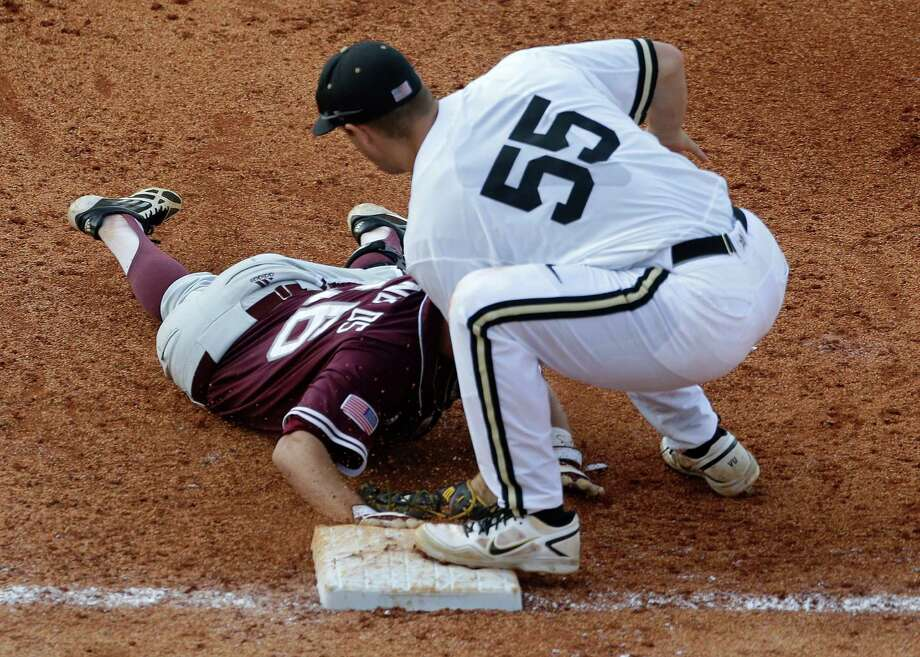 Vanderbilt's Conrad Gregor (55) tags out Texas A&M's Mikey Reynolds (16) at first on a throw from the catcher with the bases loaded in the ninth inning of their Southeastern Conference Tournament baseball game at the Hoover Met in Hoover, Ala., Wednesday, May 22, 2013. (AP Photo/Dave Martin) Photo: Dave Martin, Associated Press / AP