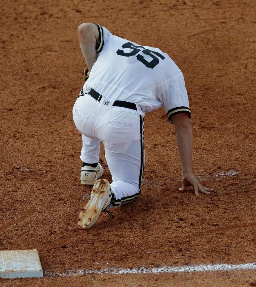 Vanderbilt's Conrad Gregor (55) kneels on the ground after a collision with a Texas A&M baserunner in the ninth inning of their Southeastern Conference Tournament baseball game at the Hoover Met in Hoover, Ala., Wednesday, May 22, 2013. (AP Photo/Dave Martin) Photo: Dave Martin, Associated Press / AP