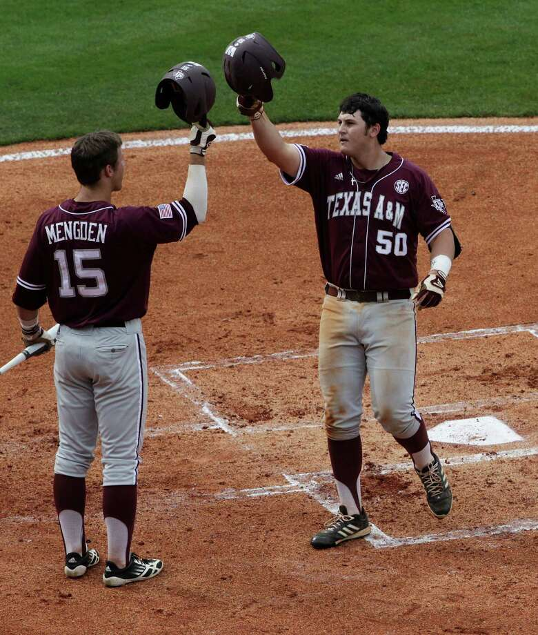 Texas A&M's Hunter Melton (50) is congratulated at home plate after a second inning home run by teammate Daniel Mengden (15) in their Southeastern Conference Tournament baseball game against Vanderbilt at the Hoover Met in Hoover, Ala., Wednesday, May 22, 2013. LSU beat Alabama 3-0. (AP Photo/Dave Martin) Photo: Dave Martin, Associated Press / AP