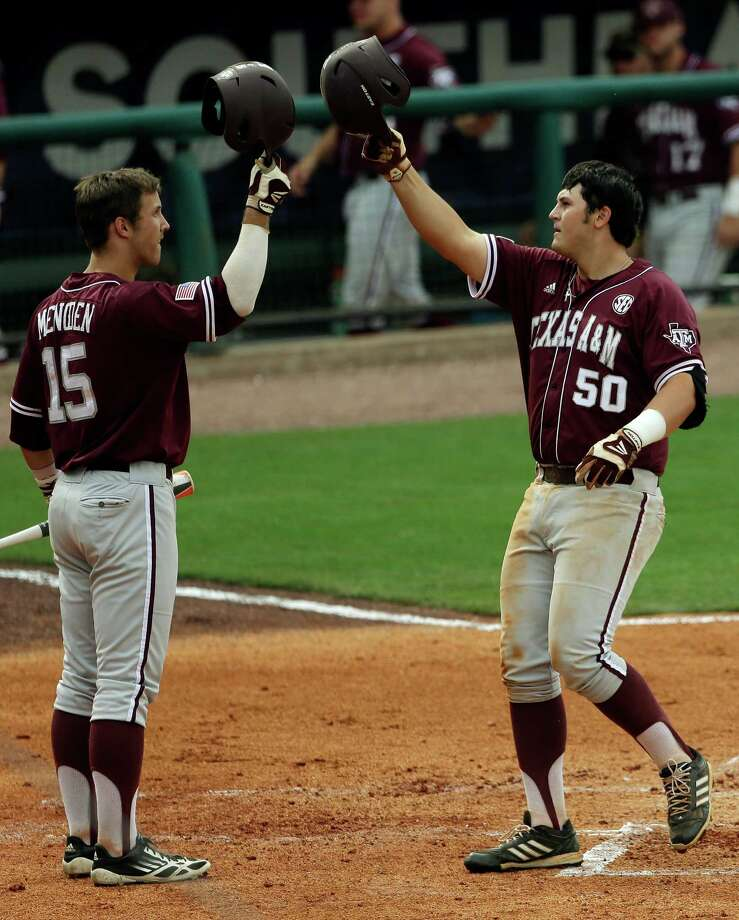 Texas A&M's Hunter Melton (50) is congratulated at home plate by teammate Daniel Mengden (15) after hitting a second-inning home run  in their Southeastern Conference Tournament college baseball game against Vanderbilt at the Hoover Met in Hoover, Ala., Wednesday, May 22, 2013. (AP Photo/Dave Martin) Photo: Dave Martin, Associated Press / AP