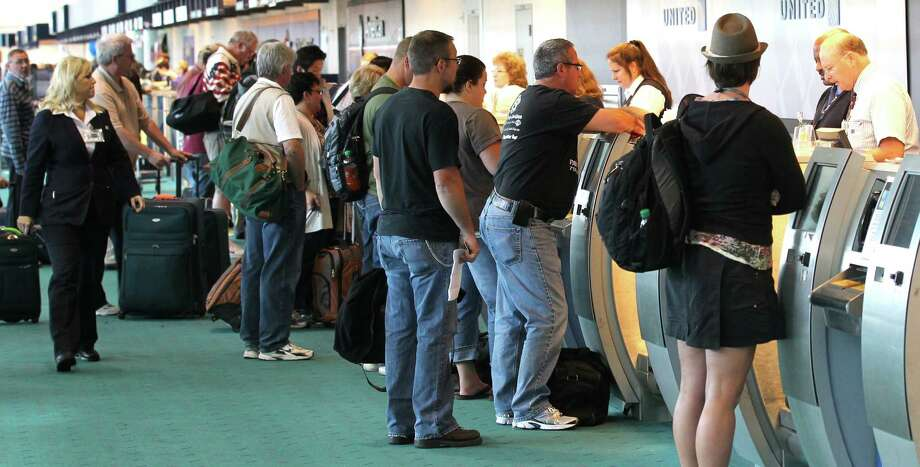 FILE - In a Friday, May 25, 2012 file photo, holiday travelers gather at the ticket counter at Portland International Airport, in Portland, Ore.  AAA estimates that another 2.3 million travelers will fly for the 2013 Memorial Day holiday, down 8 percent from last year. Photo: Rick Bowmer