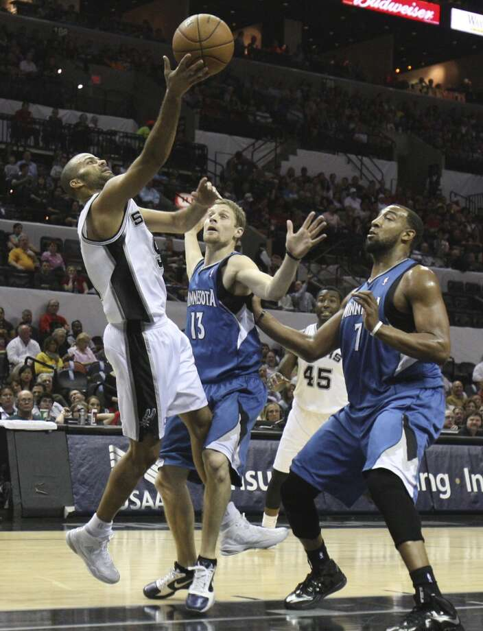 Spurs' Tony Parker (09) puts up a shot against Minnesota Timberwolves'  Luke Ridnour (13) and Derrick Williams (07) in the first quarter at the AT&T Center on Wednesday, Apr. 17, 2013.