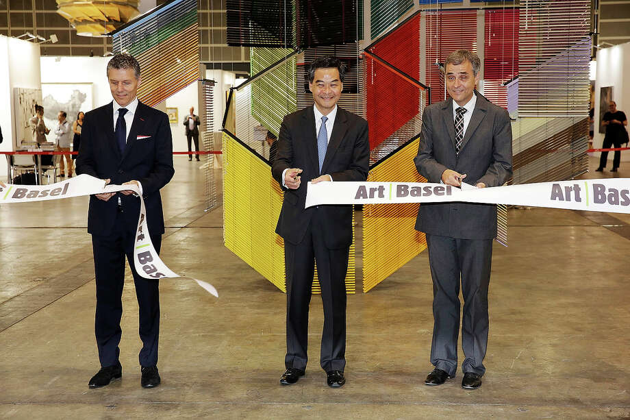 The Hon CY Leung, Chief Executive of the Hong Kong Special Administrative Region (centre) is accompanied by (left), Rene Kamm, CEO, MCH Basel Exhibition, and (right) Guy Morin, President of the Government of the Canton of Basel-Start in a ribbon cutting ceremony to open Art Basel Hong Kong, on May 22, 2013 in Hong Kong. Photo: Jessica Hromas, Getty Images / 2013 Getty Images