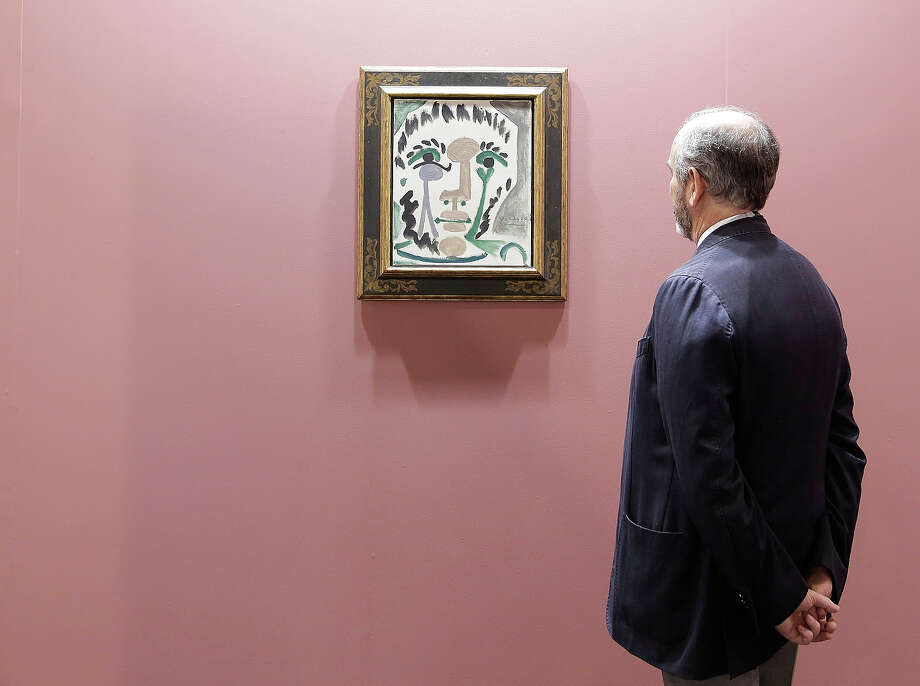 A man looks at 'Tete d'homme III' by Pablo Picasso, represented by Galeria Leandro Navarro, Madrid, at Art Basel, May 22, 2013 in Hong Kong. Photo: Jessica Hromas, Getty Images / 2013 Getty Images