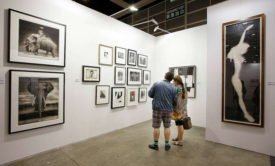 A man and woman look at photographs represented by Atlas Gallery, London, at Art Basel, May 22, 2013 in Hong Kong. Photo: Jessica Hromas, Getty Images / 2013 Getty Images