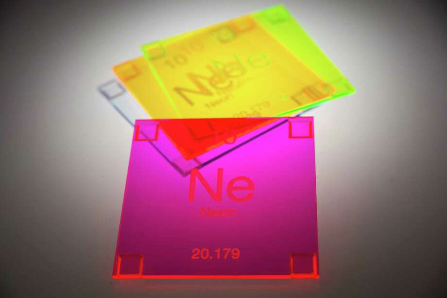 This undated publicity image provided by BPlusShop.com shows designer Byron Samayoa's coasters of neon acrylic which are etched with symbols from the Periodic Table of Elements. Small accessories like these are a great way to introduce bold, bright colors for spring decor. Photo: BPlusShop.com, Laurel Dailey
