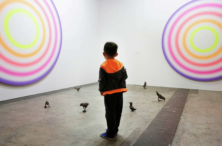 A little boy looks at art works on the floor and wall by Ugo Rondinone, which are represented by gallery Galerie Eva Presenhuber at Art Basel, May 22, 2013 in Hong Kong. Photo: Jessica Hromas, Getty Images / 2013 Getty Images