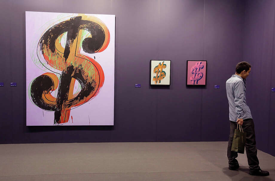 "A man looks at ""Dollar Signs"" 1980- 1982 by Andy Warhol, represented by gallery Dominique Levey Gallery, New York, at Art Basel , May 22, 2013 in Hong Kong. Photo: Jessica Hromas, Getty Images / 2013 Getty Images"