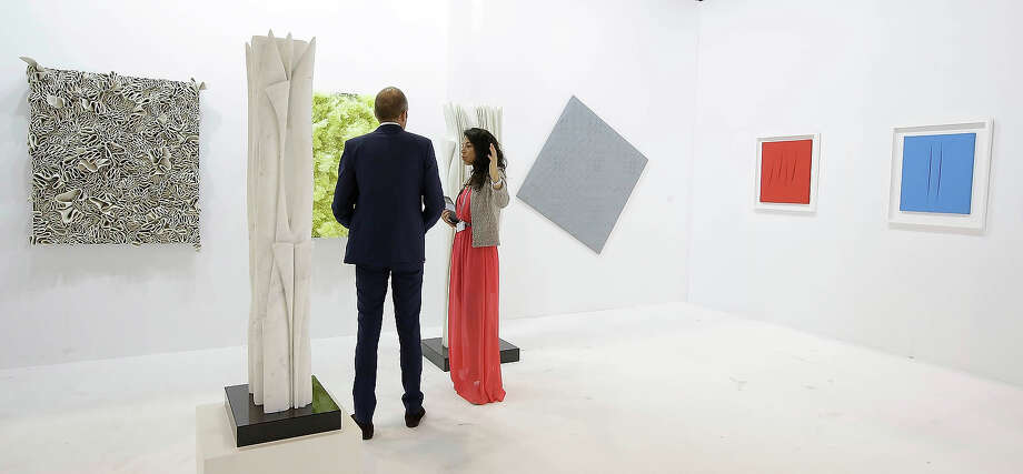 A man and woman look at art works represented by  gallery Tornabuoni Art, Paris, at Art Basel in Hong Kong,  May 22, 2013 in Hong Kong. Photo: Jessica Hromas, Getty Images / 2013 Getty Images