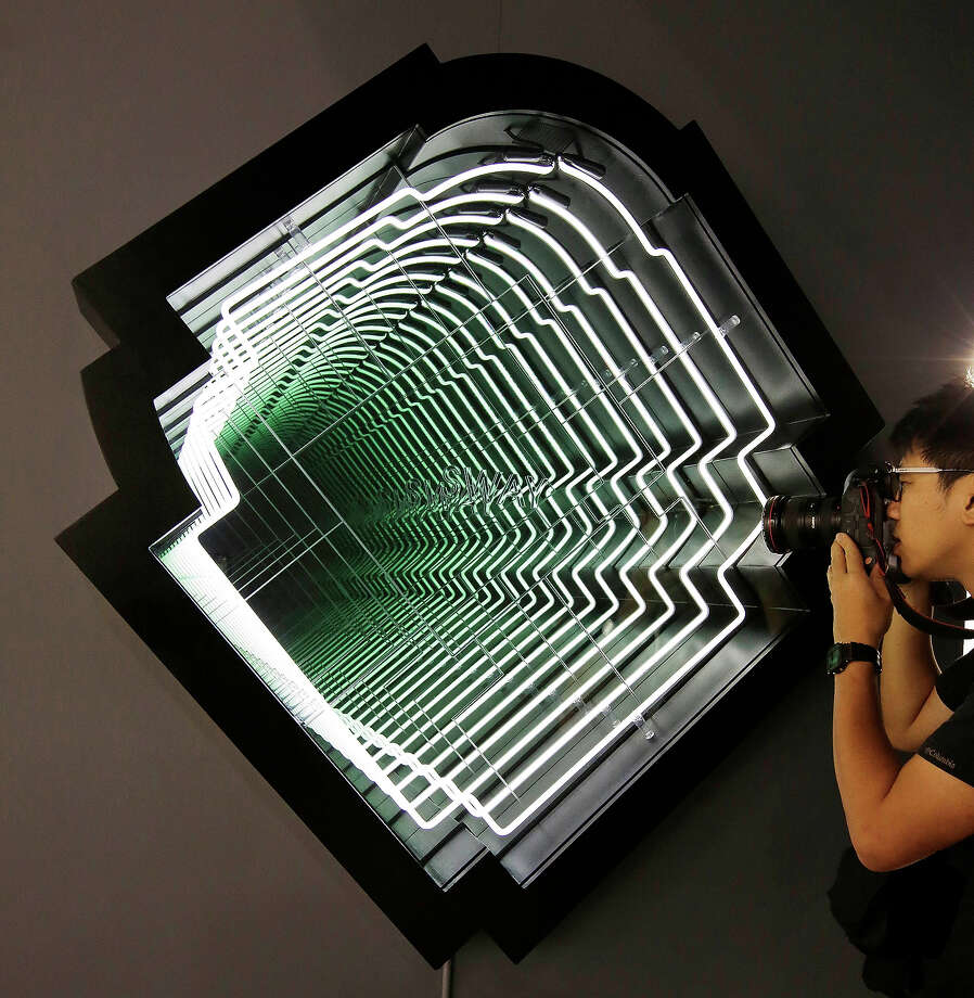 A man photographs a work called Sway by Ivan Navarro, represented by Paul Kasmin Gallery at Art Basel , May 22, 2013 in Hong Kong. Photo: Jessica Hromas, Getty Images / 2013 Getty Images
