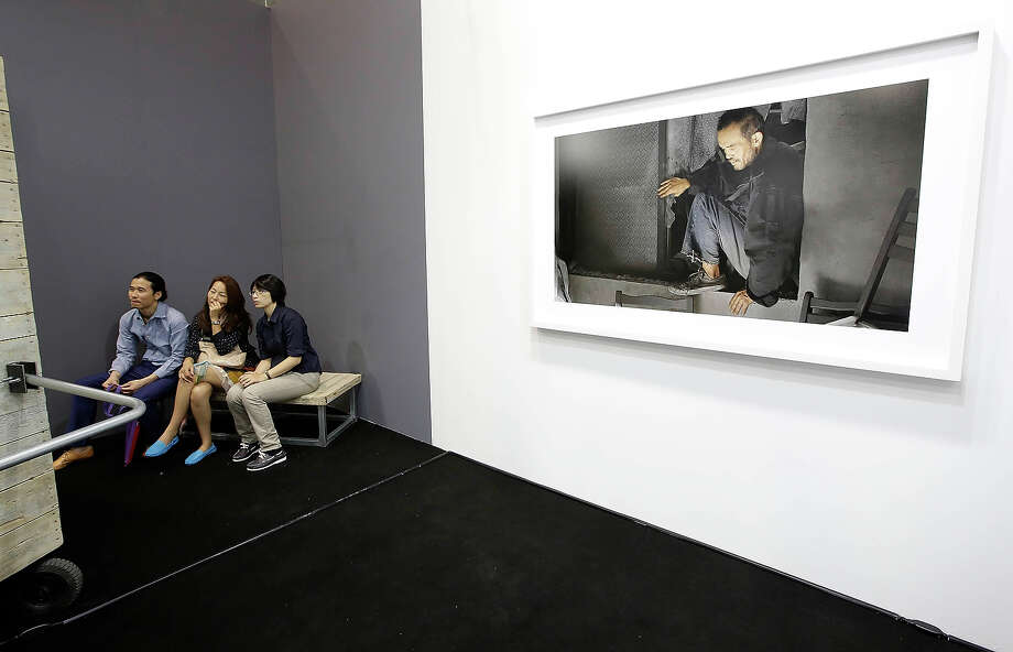 "Three people view the video work ""Friend Waton"" 2013 by  Chen Chieh-Jen, represented by Lin and Lin Gallery, Taipei, Beijin, at Art Basel in Hong Kong, May 22, 2013 in Hong Kong. Photo: Jessica Hromas, Getty Images / 2013 Getty Images"