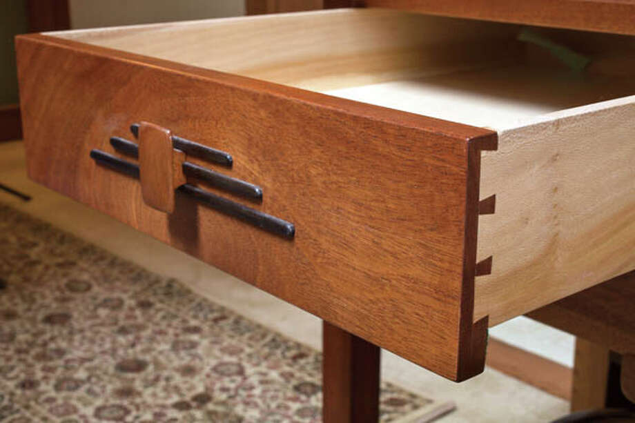 An end table with ebony inlays made by John Olenik in the living room of his home on Monday April 15, 2013 in Ballston Spa, NY. notice the L brackets under the drawer on this table. They're a hallmark of the Arts and Crafts style and are on display instead of hidden. Photo: Philip Kamrass / Philip Kamrass 2013