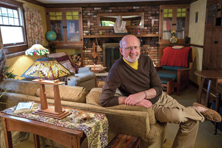 John Olenik sits in his home on Monday April 15, 2013 in Ballston Spa, NY.  Below, Olenik in his first-floor living room. In the foreground, a lamp whose base — you guessed it — he built. Photo: Philip Kamrass / Philip Kamrass 2013