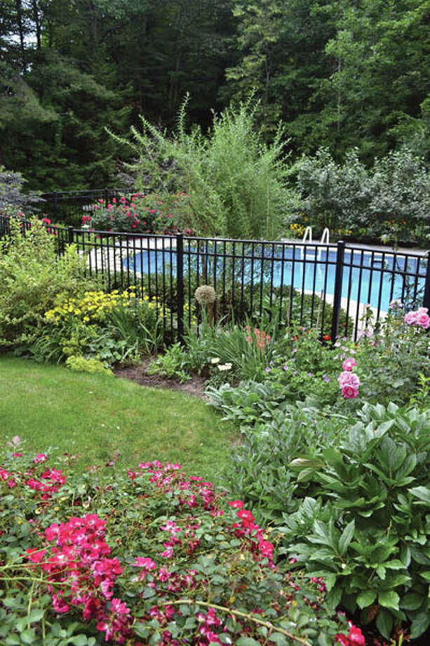 "Don't worry about precision, says Gillian. ""Take the line of least resistance."" The yard of Gillian and Sidney Woodcock of Niskayuna  is awash in roses, coreopsis, daisies, hydrangeas and more."