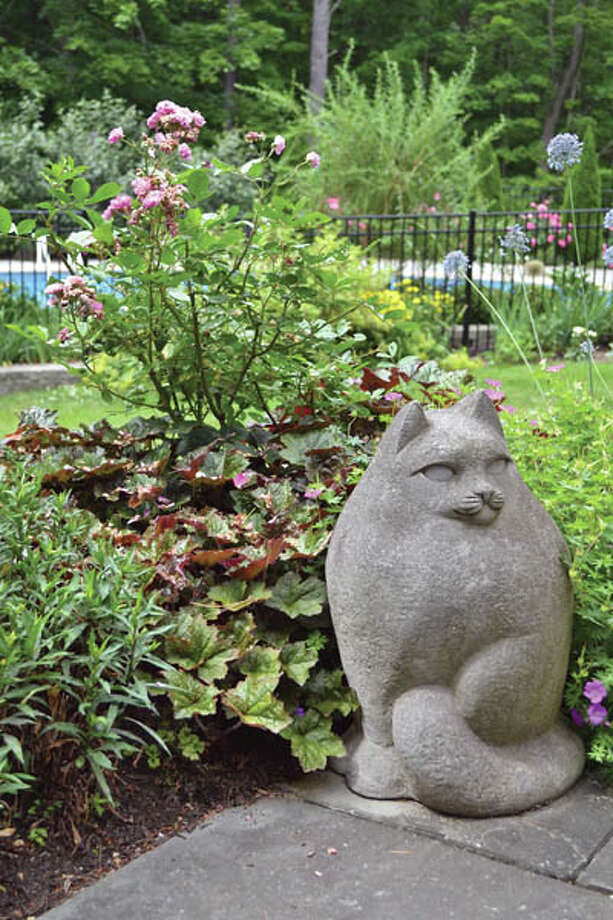 Bertie the cat loved the garden. Now this statue, also named Bertie, watches over the plantings.
