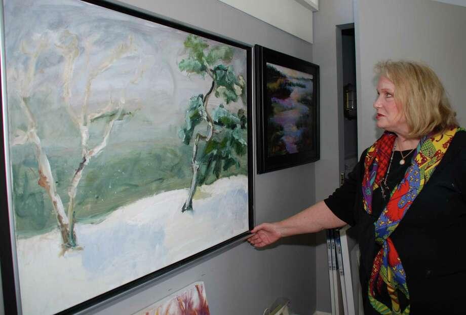 "Artist Jan Dilenschneider straightens her award winning painting, ""A Birch and a Pine in a Whiteout,"" in her studio in Darien, Conn., on May 3, 2013. Photo: Jeanna Petersen Shepard / Darien News freelance Jeanna Petersen Shepard"