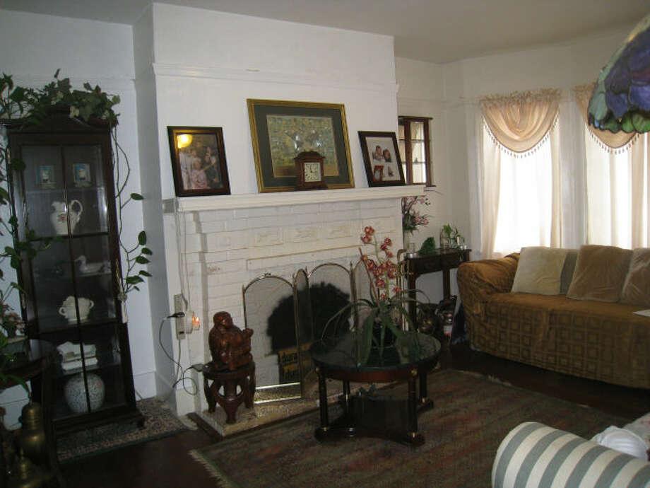 Living room with fireplace. Photos via Elizabeth Machado, Figueroa Realty/Redfin/MLS