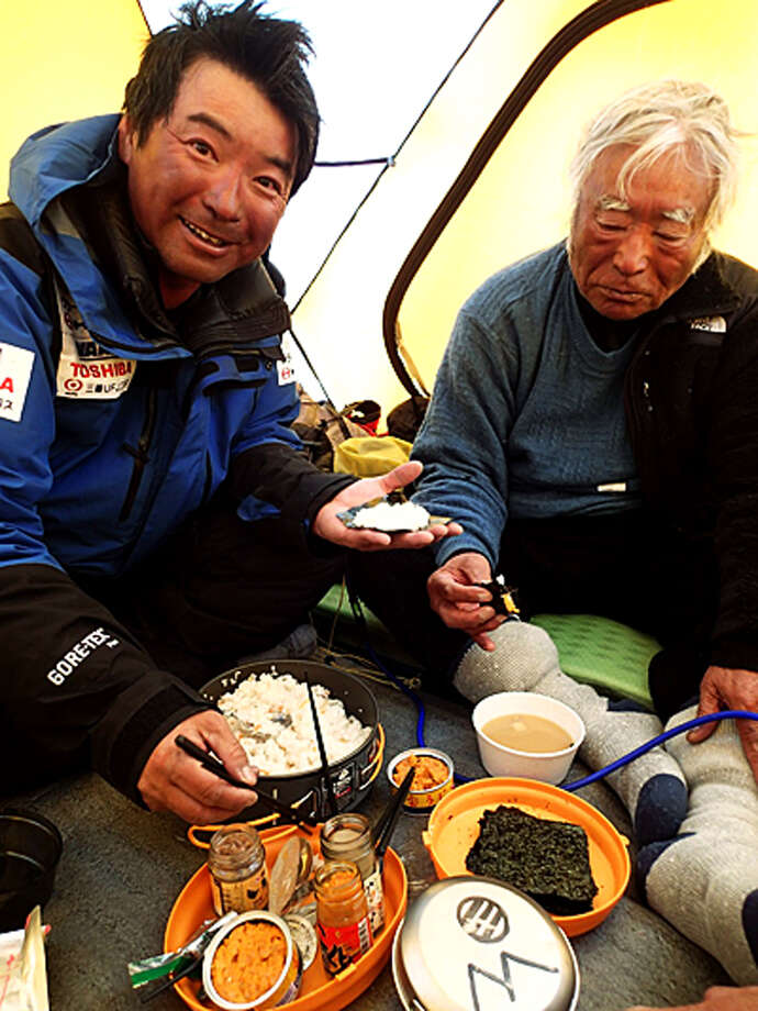 In this Tuesday, May 21, 2013 photo distributed by Miura Dolphins, 80-year-old Japanese extreme skier Yuichiro Miura, right, and his son, Gota, eat rolled sushi at their South Col camp at 8,000 meters (26,247 feet) during their attempt to scale the summit of Mount Everest. According to his management office, Miura plans to reach the 8,850-meter (29,035-foot) peak on Thursday, May 23 to be the world's oldest person to climb the world's highest peak. His rival, 81-year-old Min Bahadur Sherchan, from Nepal, who nabbed the record just before he could in 2008, was at the base camp preparing for his own attempt on the summit next week. (AP Photo/Miura Dolphins)  MANDATORY CREDIT Photo: AP / Miura Dolphins