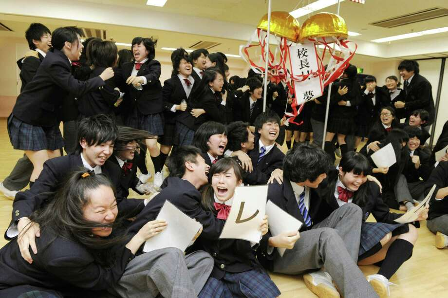 Students celebrate after a report that 80-year-old Japanese mountaineer Yuichiro Miura conquered the summit of Mount Everest, at CLARK Memorial International High School in Tokyo Thursday, May 23, 2013. Miura on Thursday became the oldest person to reach the top of Mount Everest - although his record may last only a few days. An 81-year-old Nepalese man, who held the previous record, plans his own ascent next week. Miura is the principal of the school. (AP Photo/Kyodo News)  JAPAN OUT, MANDATORY CREDIT Photo: AP / Khyodo News