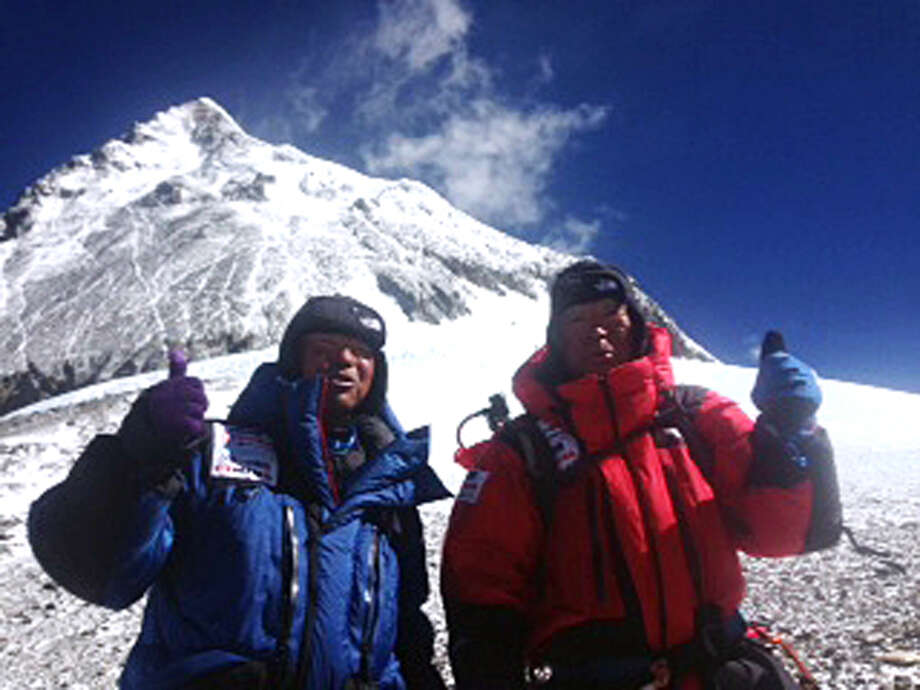 In this May 22, 2013 photo distributed by Miura Dolphins Co. Ltd., 80-year-old Japanese extreme skier Yuichiro Miura, right, and his son, Gota pose at their South Col camp at 8,000 meters (26,247 feet) before their departure for Camp 5 during their attempt to scale the summit of Mount Everest. Miura, who climbed Mount Everest five years ago, but just missed becoming the oldest man to reach the summit, was back on the mountain Wednesday to make another attempt at the title. (AP Photo/Miura Dolphins Co. Ltd.)  MANDATORY CREDIT Photo: AP / MIURA DOLPHINS CO.,LTD.