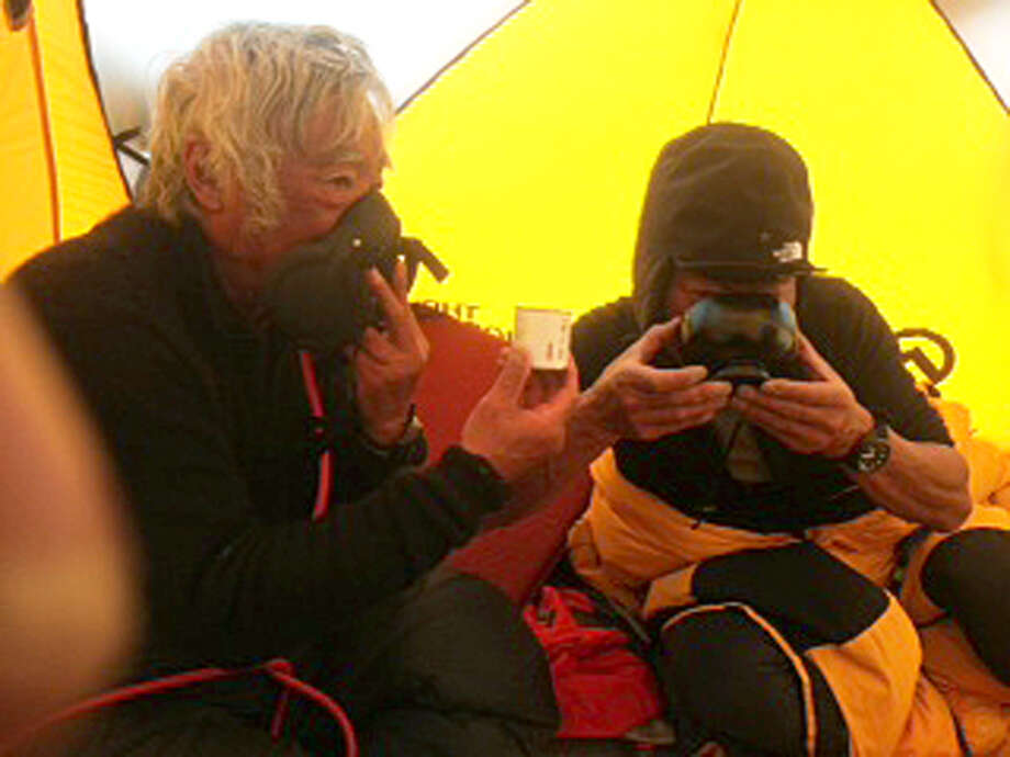 In this May 22, 2013 photo distributed by Miura Dolphins Co. Ltd., 80-year-old Japanese extreme skier Yuichiro Miura, left, uses oxygen mask and his son, Gota sips green tea as they take a rest in a tent at their South Col camp at 8,000 meters (26,247 feet) before their departure for Camp 5 during their attempt to scale the summit of Mount Everest. Miura, who climbed Mount Everest five years ago, but just missed becoming the oldest man to reach the summit, was back on the mountain Wednesday to make another attempt at the title. (AP Photo/Miura Dolphins Co. Ltd.)  MANDATORY CREDIT Photo: AP / MIURA DOLPHINS CO.,LTD.