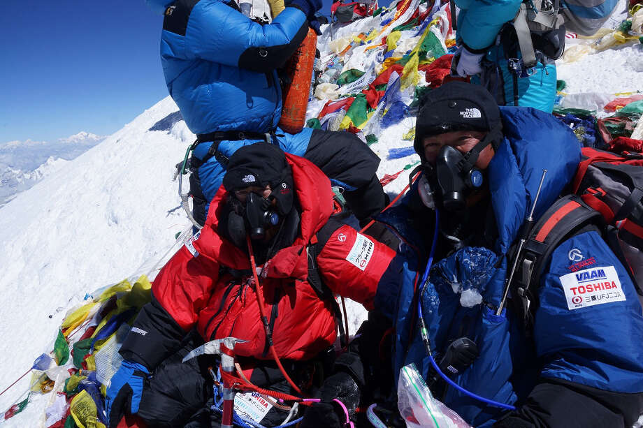 In this photo distributed by MIURA DOLPHINS CO., LTD., 80-year-old Japanese extreme skier Yuichiro Miura, left, who has had four heart operations in recent years, and his son, Gota, are atop the summit of Mount Everest as he becomes the oldest person to climb the world's tallest mountain Thursday, May 23, 2013. Miura, who also conquered the 29,035-foot (8,850-meter) peak when he was 70 and 75, reached the summit at 9:05 a.m. local time, according to a Nepalese mountaineering official and Miura's Tokyo-based support team. (AP Photo/MIURA DOLPHINS CO., LTD.)  MANDATORY CREDIT Photo: AP / Miura Dolphins C.. Ltd