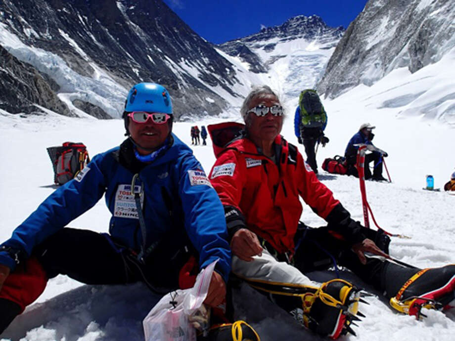 In this Friday, May 17, 2013 photo distributed by Miura Dolphins, 80-year-old Japanese adventurer Yuichiro Miura, right, and his son, Gota, rest on their way to a camp at 6,500 meters (21,325 feet) from a camp at 6,050 meters (19,849 feet) during their attempt to scale the summit of Mount Everest. According to his management office, Miura plans to reach the 8,850-meter (29,035-foot) peak on Thursday, May 23 to be the world's oldest person to reach the world's highest peak. (AP Photo/Miura Dolphins)  MANDATORY CREDIT Photo: AP / Miura Dolphins
