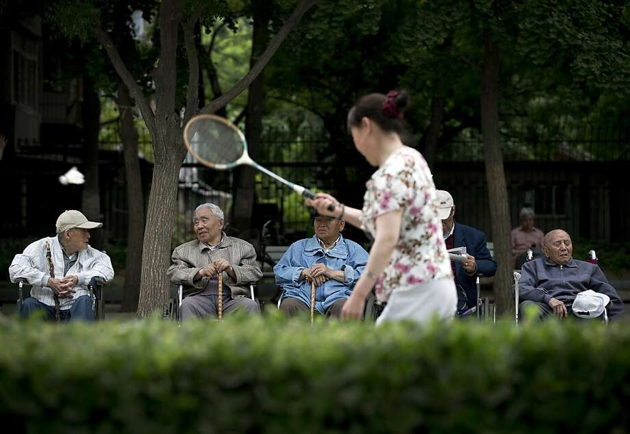 Watch the birdie:A badminton match draws an elderly male audience at a Beijing park. Photo: Andy Wong, Associated Press