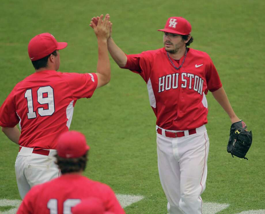 The University of Houston's Ryan Vruggink left, slaps hands with starting pitcher Austin Pruitt right, as U of H plays East Carolina University during the fifth inning of the 2013 Conference USA Championship at Rice University's Reckling Park Thursday, May 23, 2013, in Houston. Photo: James Nielsen, Houston Chronicle / © 2013  Houston Chronicle