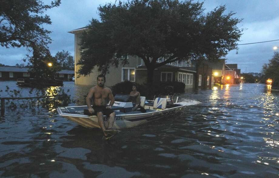 Two men use a boat to explore a street flooded by Hurricane Irene Saturday, Aug. 27, 2011 in Monteo, N.C. (AP Photo/John Bazemore) Photo: John Bazemore, Associated Press