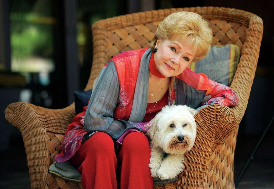 "In this Tuesday, May 21, 2013 photo, Debbie Reynolds, a cast member in the film ""Behind the Candelabra,"" poses for a portrait with her dog, Dwight, in Beverly Hills, Calif. Reynolds plays Frances, the mother of the pianist and vocalist, Liberace. HBO debuts ""Behind the Candelabra"" in the US, Sunday, May 26, 2013. (Photo by Chris Pizzello/Invision/AP) Photo: Chris Pizzello"