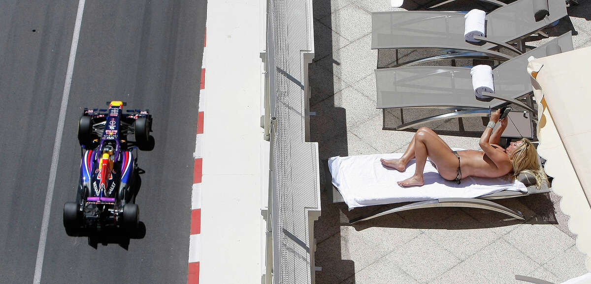 Red Bull driver Sebastian Vettel of Germany steers his car as a woman sunbathes on a terrace during the second free practice at the Monaco racetrack, in Monaco, Thursday, May 23, 2013. The 2013 Monaco Grand Prix Formula One race will be held on Sunday.