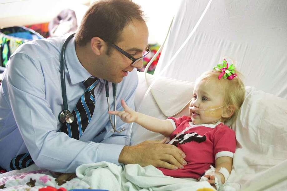 Dr. Brent Mothner, a hospitalist, checks on Lilly Kilgore, 2, at Texas Children's Hospital. Photo: Brett Coomer, Staff / © 2013 Houston Chronicle