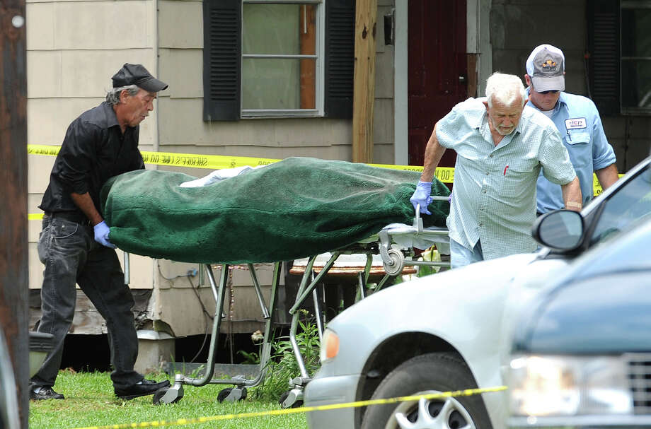 The body of a woman is taken from a home in Hamshire after a shooting Thursday morning. The Jefferson County Sheriff's Department is conducting an investigation into the incident. Photo taken Thursday, May 23, 2013 Guiseppe Barranco/The Enterprise Photo: Guiseppe Barranco, STAFF PHOTOGRAPHER / The Beaumont Enterprise