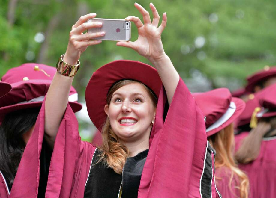 Graduate Andrea Goosens of Elmira photographs her classmate during Albany Medical College commencement at the Saratoga Performing Arts Center in Saratoga Springs, NY, Thursday May 23, 2013.  (John Carl D'Annibale / Times Union) Photo: John Carl D'Annibale / 10022119A