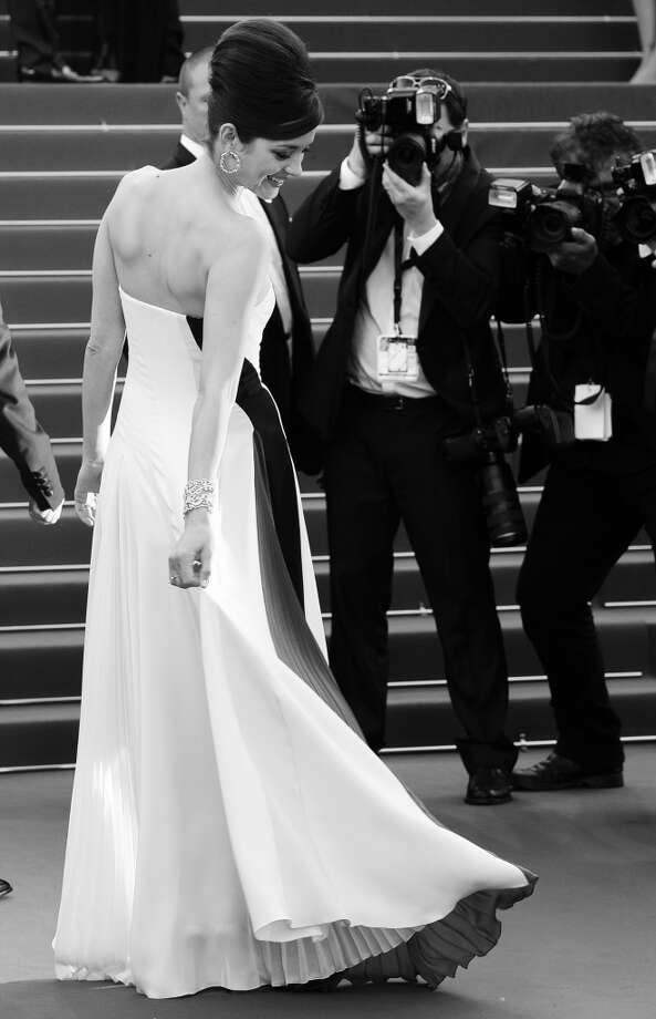 "French actress Marion Cotillard adjusts her dress on May 20, 2013 as she arrives for the screening of the film ""Blood Ties"" at this year's Cannes festival."