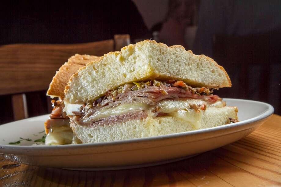 Muffaletta sandwich: Foccacia, ham, salami, mortadella, provolone, mozzarella, olive salad. Half (pictured) $12.00, Whole $20.00.