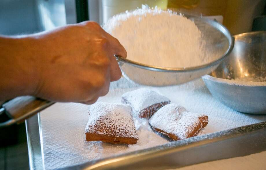 Beignets being dusted.