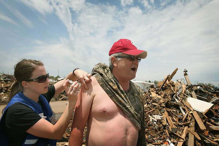 Jennifer Dudgeon of the Cleveland County Health Department delivers a tetanus shot to Moore, Okla., resident Tim Jones. Photo: Scott Olson, Getty Images