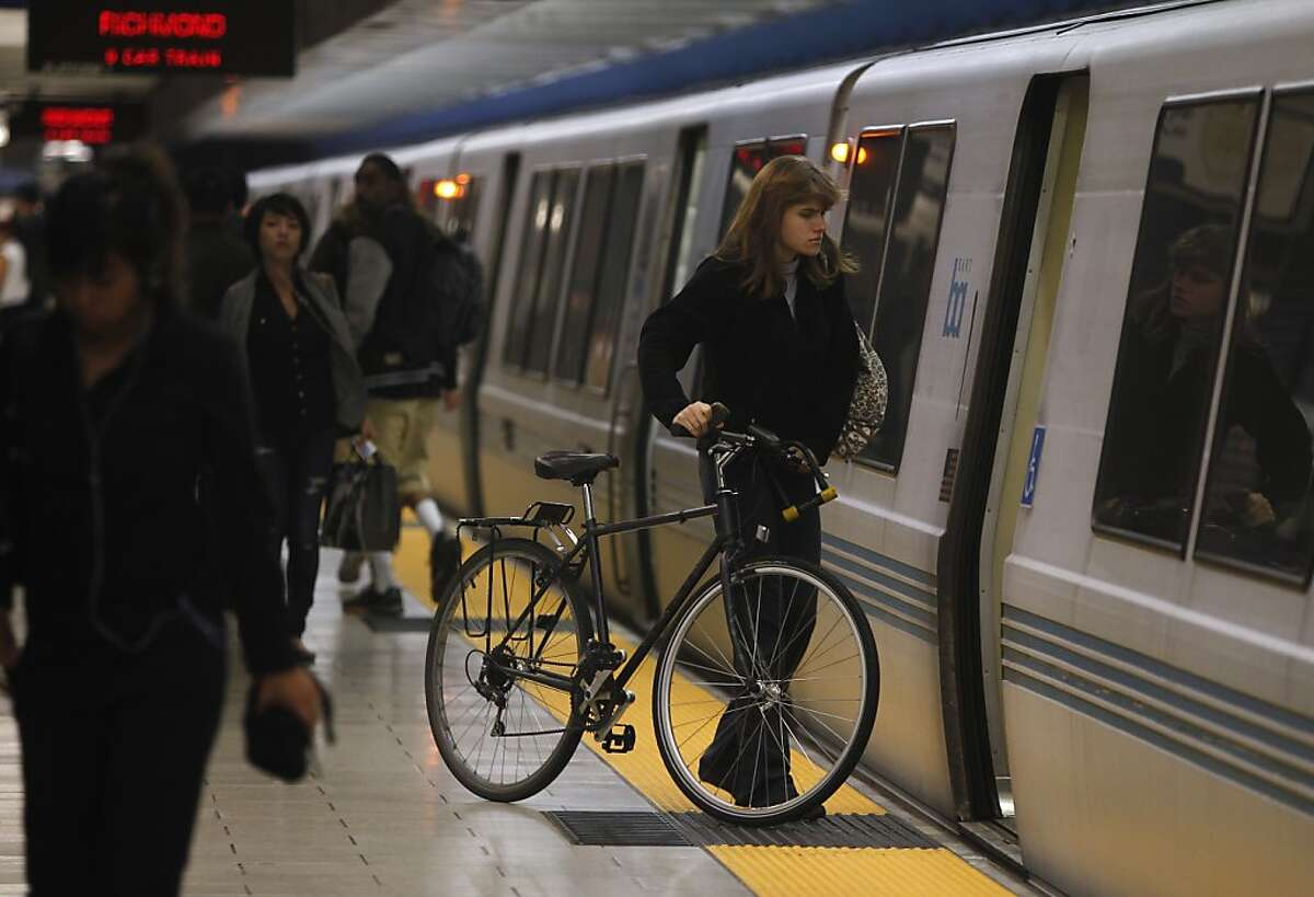 Sophie Stroik boards a Richmond-bound train with her bicycle at the 19th Street BART station in Oakland, Calif. on Wednesday, March 13, 2013.