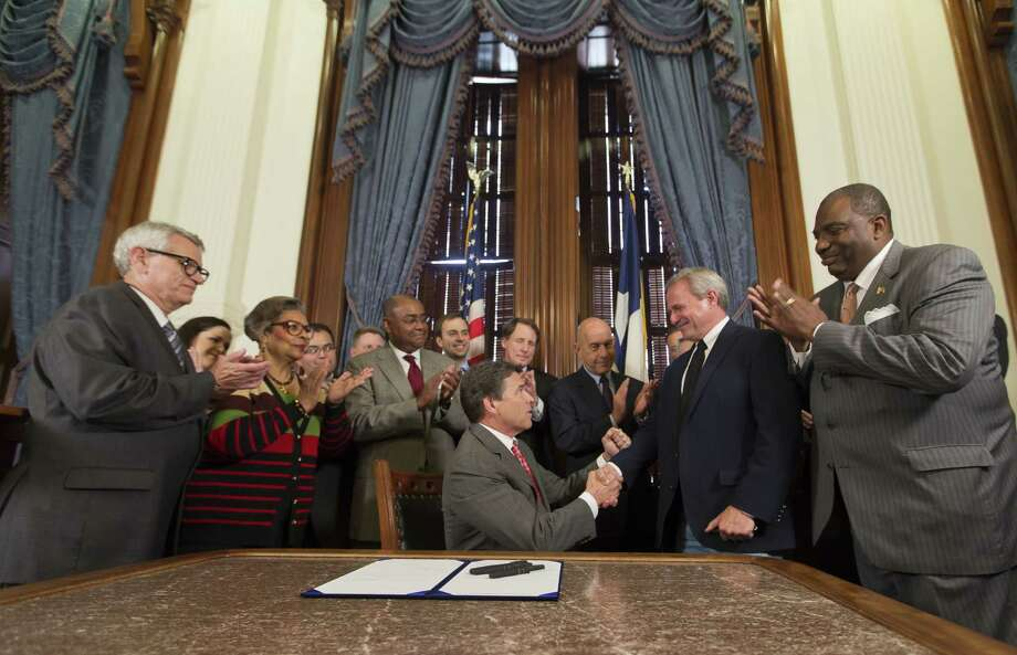 Gov. Rick Perry presents Michael Morton with a pen after signing the Michael Morton Act into law. Morton spent 25 years in prison after being wrongfully convicted of the 1986 murder of his wife, Christine. Photo: Ricardo B. Brazziell, Associated Press