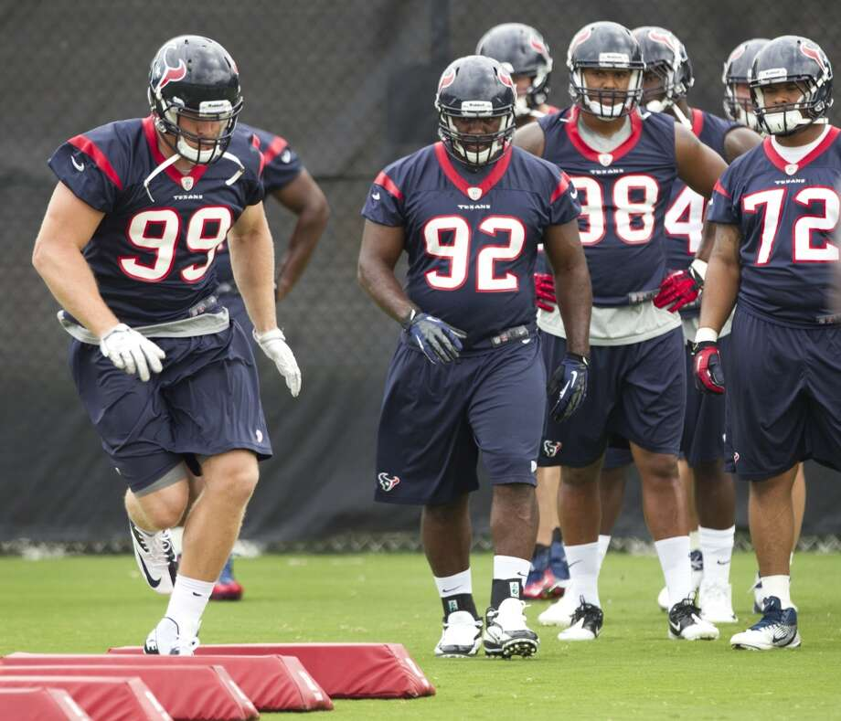 Texans defensive end J.J. Watt (99) leads the way through an agility drill.