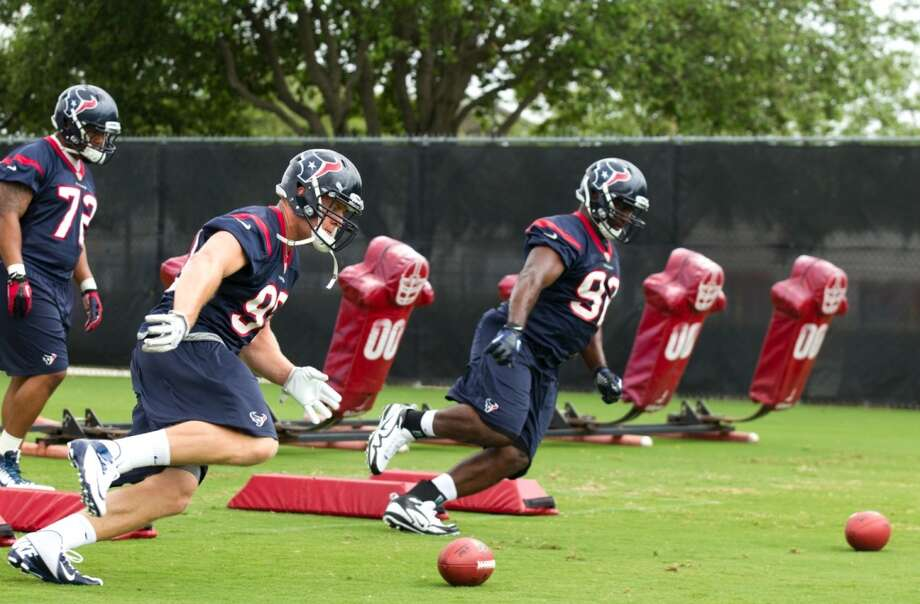 Texans defensive end J.J. Watt (99) and nose tackle Earl Mitchell (92) run a drill .