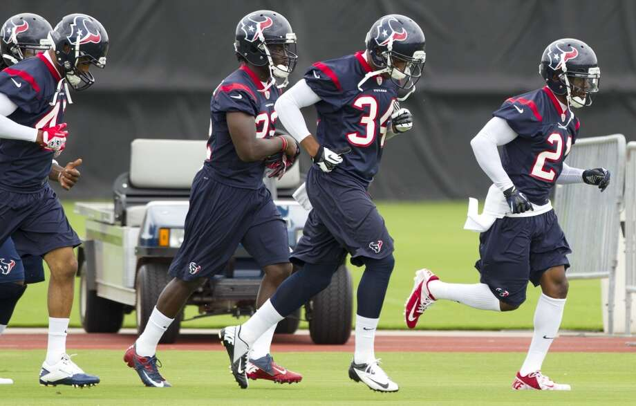 Texans defensive backs run across the field.