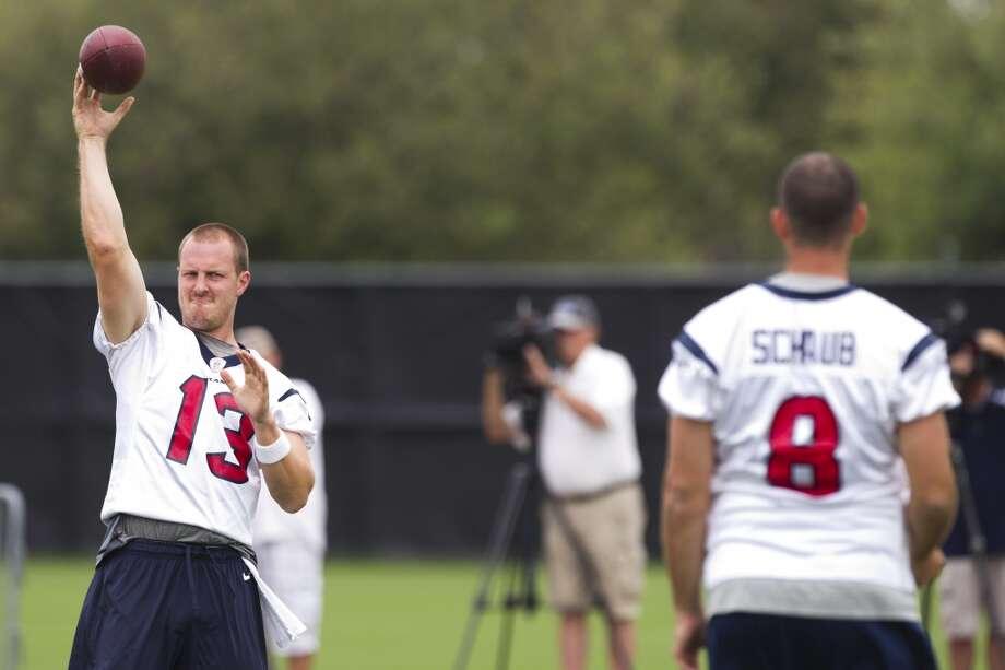 Texans quarterbacks T.J. Yates (13) and Matt Schaub (8) play catch before practice.