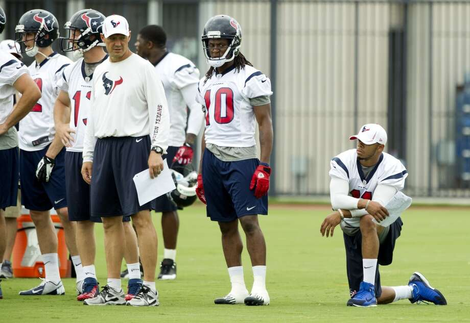 Texans wide receiver DeVier Posey, right, kneels as he watches practice.