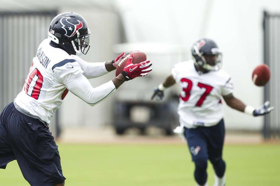 Texans wide receiver Andre Johnson, left, and running back Ray Graham (37) reach out to catch passes.